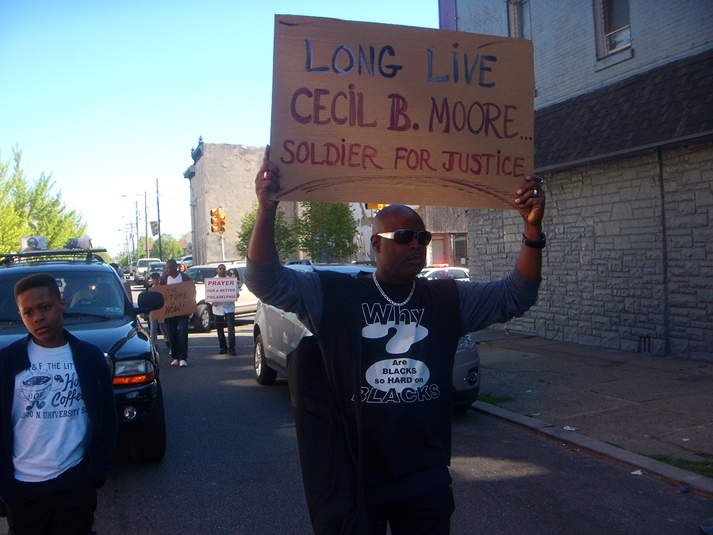 Man holding sign stating long live Cecil B. Moore soldier for justice