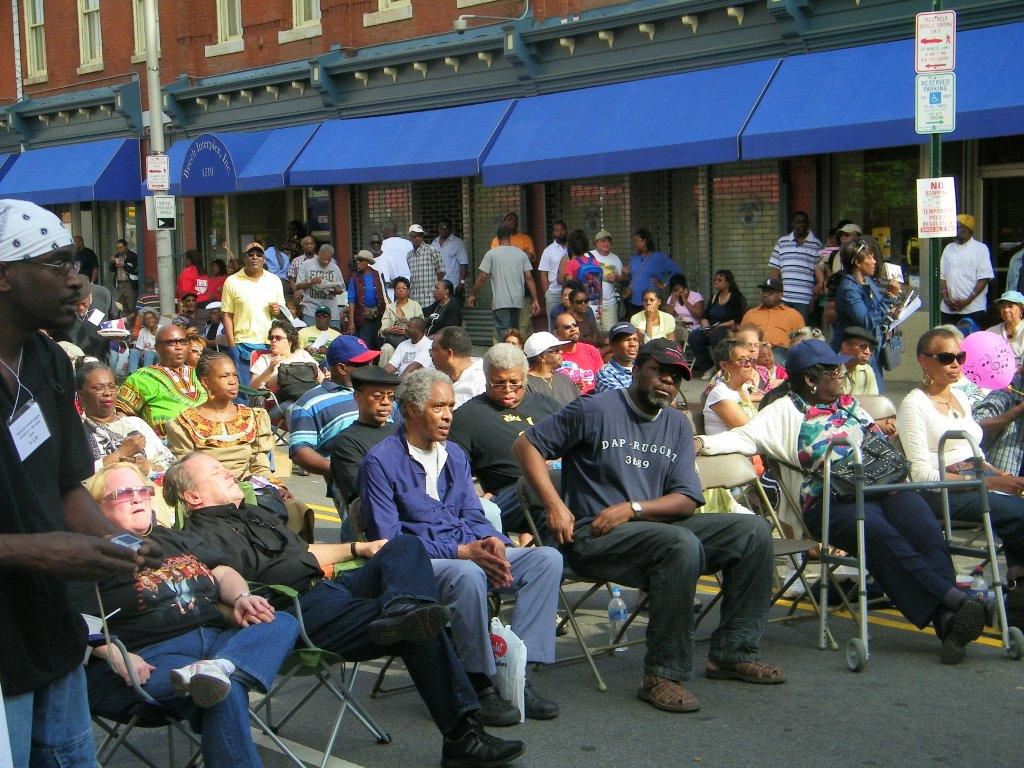 People in chairs on street at community event