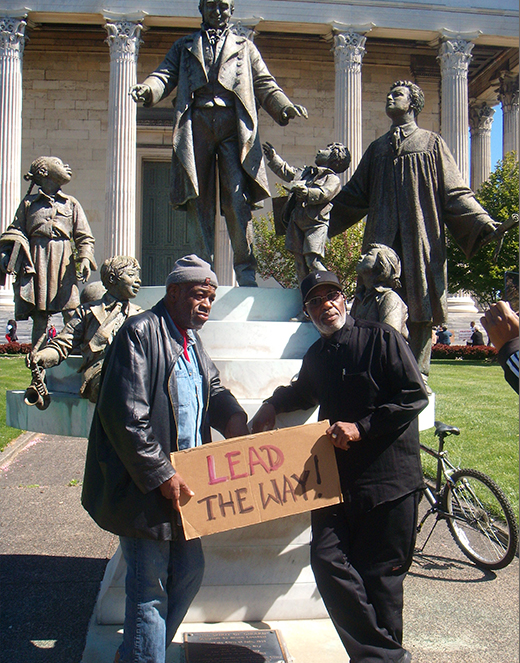 2 men holding sign that says Lead the Way